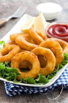 Anneaux de calamars frits avec de la laitue et du ketchup sur une surface en bois