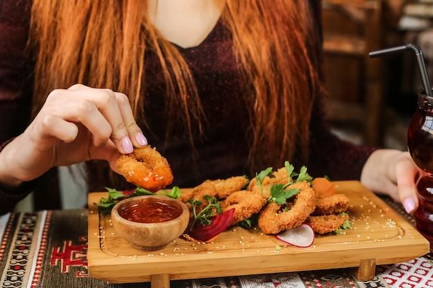 Anneaux de calamars frits avec radis, persil, sésame et sauce chili douce