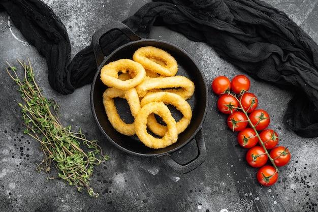Anneaux de calmar ou oignon dans la chapelure ingrédients mis sur poêle à frire en fonte, sur fond de table en pierre noire noire, vue de dessus mise à plat
