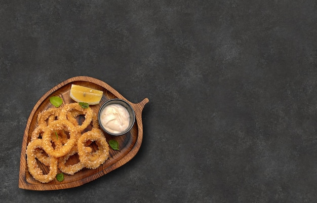 Anneaux de calmar en pâte avec sauce et citron sur planche de bois sur fond gris avec une place pour le texte vue de dessus