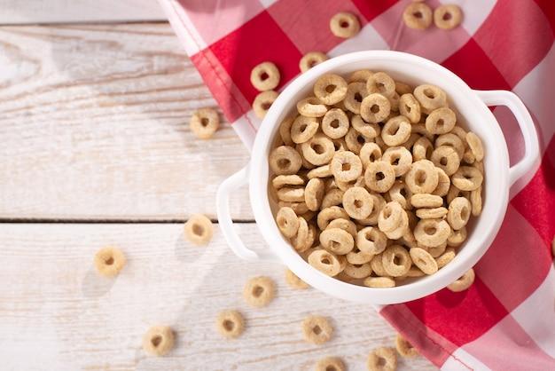 Anneaux de céréales sur fond de bois clair avec nappe rouge dans une assiette et éparpillés sur la table avec les rayons du soleil. petit-déjeuner sain pour les enfants.