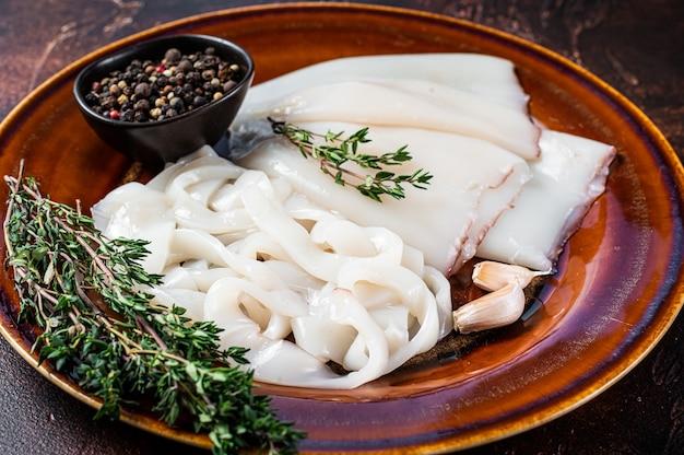 Anneaux crus tranchés calamars dans une assiette rustique au romarin