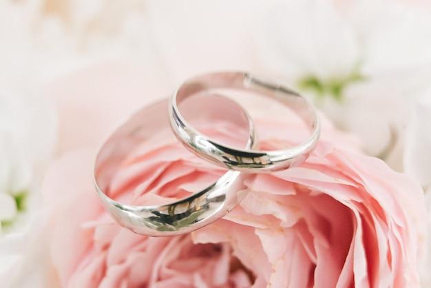 Anneaux de fiançailles de mariage et fond de bouquet de mariage de fleurs