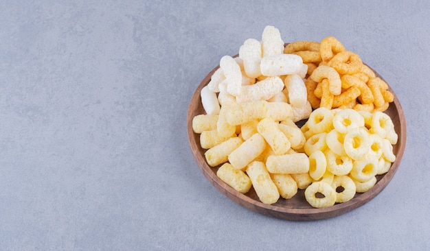 Anneaux de maïs et bâtonnets de maïs dans une assiette en bois sur la surface en marbre