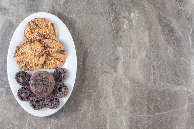 Anneaux de maïs et biscuits faits maison sur une assiette en marbre.