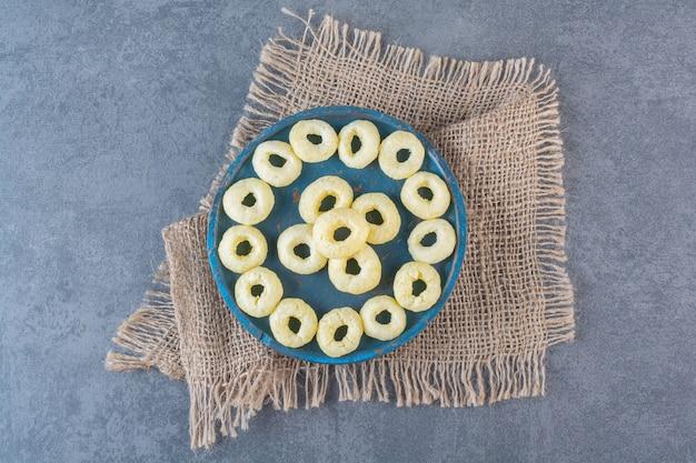 Anneaux de maïs savoureux sur une plaque en bois sur la texture, sur la surface en marbre.