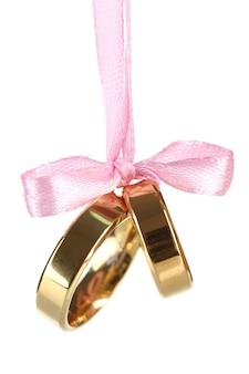 Anneaux de mariage attachés avec du ruban isolé sur blanc