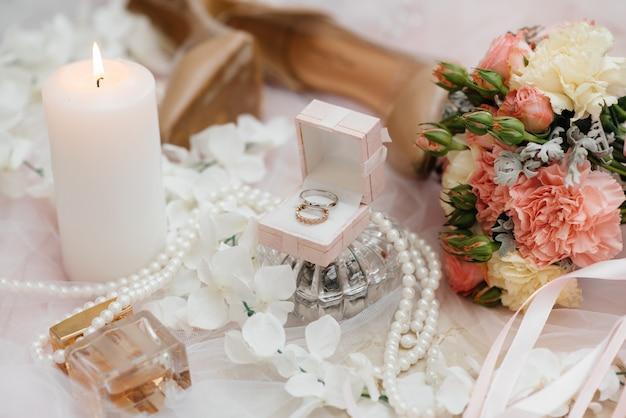 Anneaux de mariage et autres accessoires en gros plan lors de la réunion de la mariée. mariage.