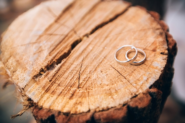 Anneaux de mariage. bijoux en or blanc et jaune. bague de mariage sur la texture en bois. talon en bois