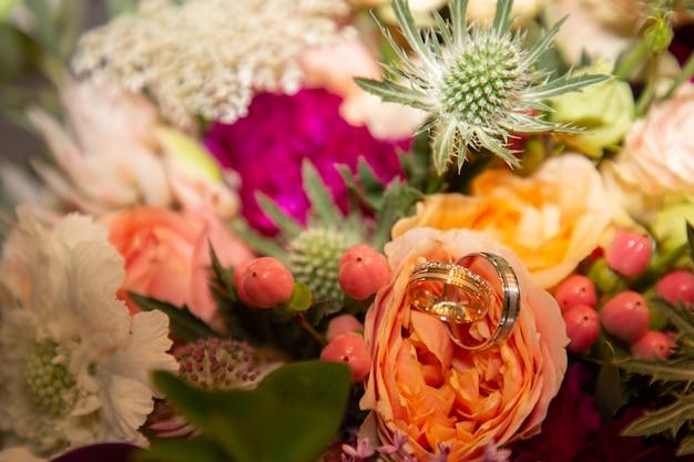 Anneaux de mariage sur le bouquet de fleurs de mariage