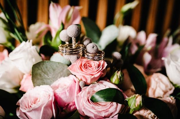 Anneaux de mariage sur un bouquet de fleurs de roses