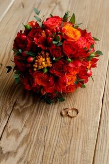 Anneaux de mariage et bouquet de fleurs rouges sur fond de bois