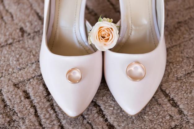 Anneaux de mariage sur des chaussures de mariage