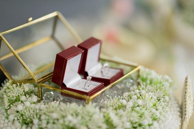 Anneaux de mariage dans une belle boîte en verre sur des fleurs avec un arrière-plan flou