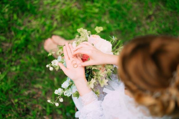 Anneaux de mariage dans une boîte en bois pour anneaux entre les mains de la mariée