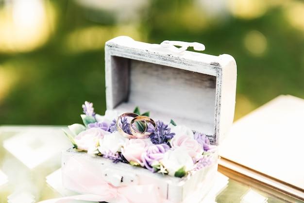 Anneaux de mariage dans une boîte avec des fleurs, décor et détails de la cérémonie de mariage