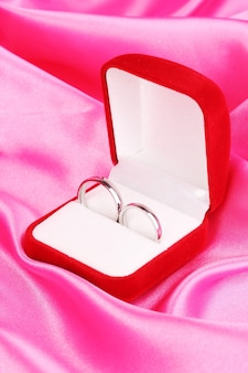 Anneaux de mariage dans une boîte rouge sur l'espace en tissu rose