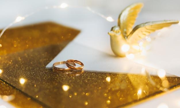 Anneaux de mariage dorés sur fond doré avec oiseau jouet et décorations.