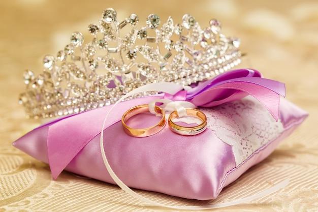 Anneaux de mariage dorés sur l'oreiller en dentelle violette. concept de mariage