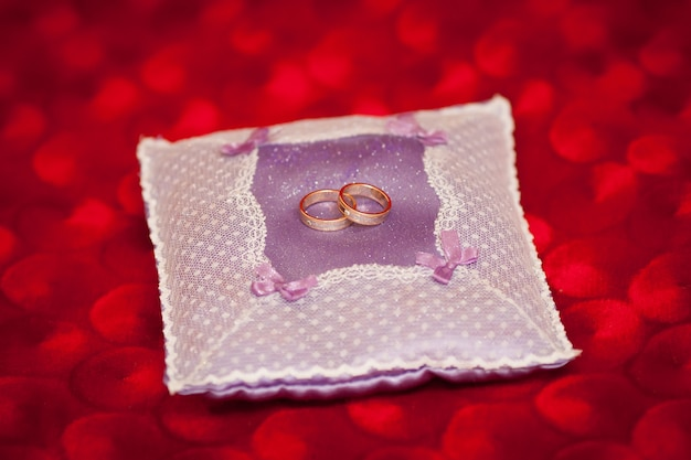 Anneaux de mariage dorés sur un petit oreiller violet décoré. concept de mariage