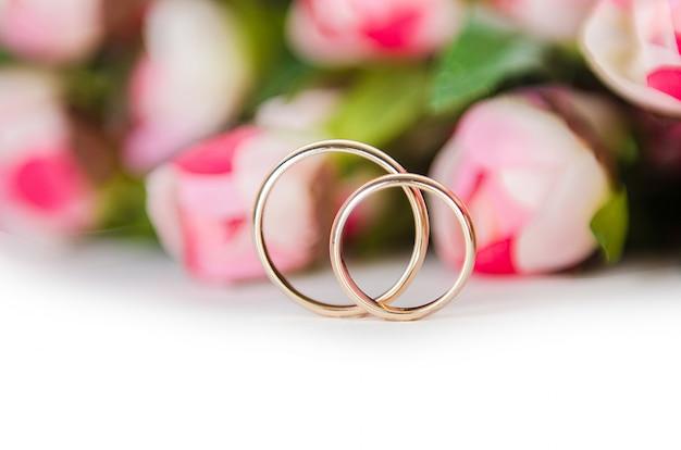 Anneaux de mariage et fleurs isolés on white
