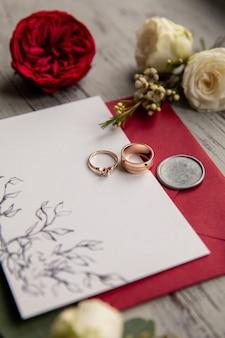Anneaux de mariage sur invitation blanc et rouge près de fleurs rouges
