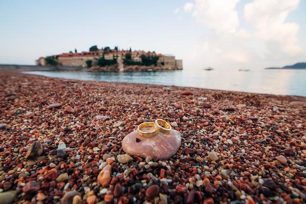 Anneaux de mariage de jeunes mariés sur des galets de plage