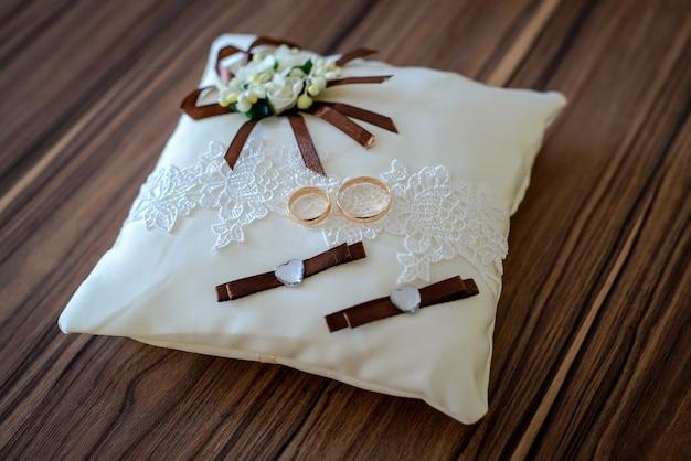 Anneaux de mariage d'or sur un beau coussin blanc rubans et fleurs marron