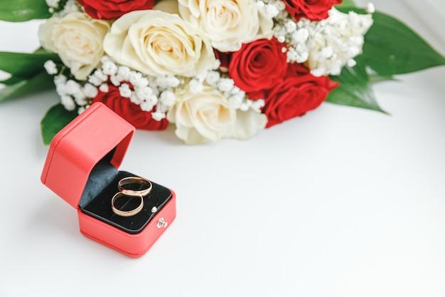 Anneaux de mariage d'or et bouquet de fleurs dans des couleurs rouges blanches se trouvant sur le fond blanc. déclaration d'amour, printemps. carte de mariage, voeux de la saint-valentin. anneaux de mariage. détails du jour du mariage.