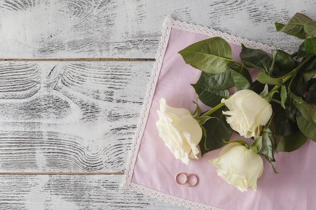 Anneaux de mariage en or sur un bouquet de roses blanches