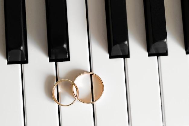 Anneaux de mariage en or sur le clavier du piano.