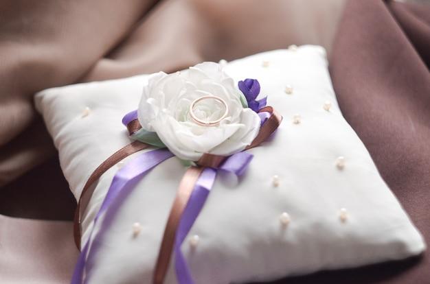 Anneaux de mariage en or sur un coussin blanc avec un arc et des perles