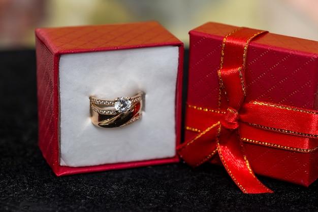 Anneaux de mariage d'or dans une boîte cadeau rouge sur fond noir