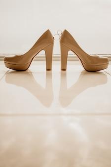 Anneaux de mariage or entre paire de chaussures à talons hauts blancs