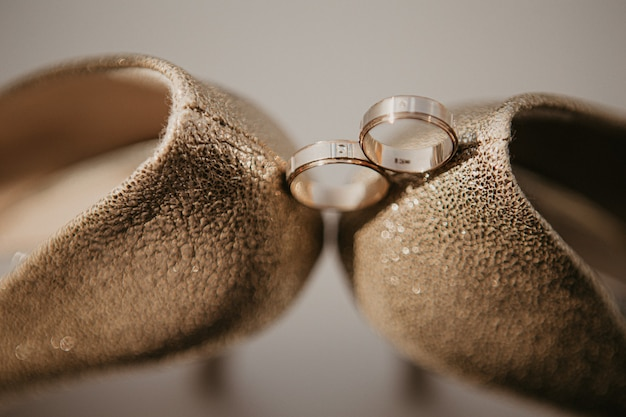 Anneaux de mariage or entre paire de chaussures à talons hauts dorés