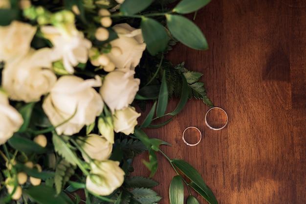 Anneaux de mariage d'or sur un fond en bois avec bouquet de fleurs
