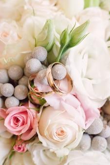 Anneaux de mariage or en gros plan de fleurs