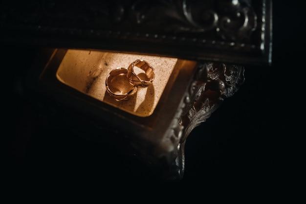 Les anneaux de mariage en or reposent sur une boîte à bijoux ancienne. anneaux de mariage pour les cérémonies.