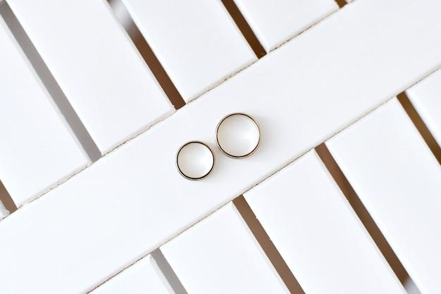 Les anneaux de mariage en or se trouvent sur un fond blanc