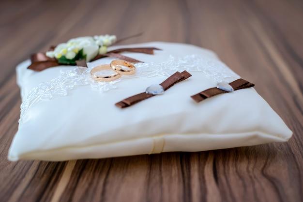 Anneaux de mariage sur oreiller blanc