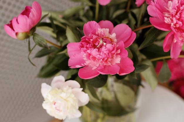 Anneaux de mariage sur pivoines roses