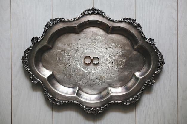 Anneaux de mariage sur un plateau en métal.