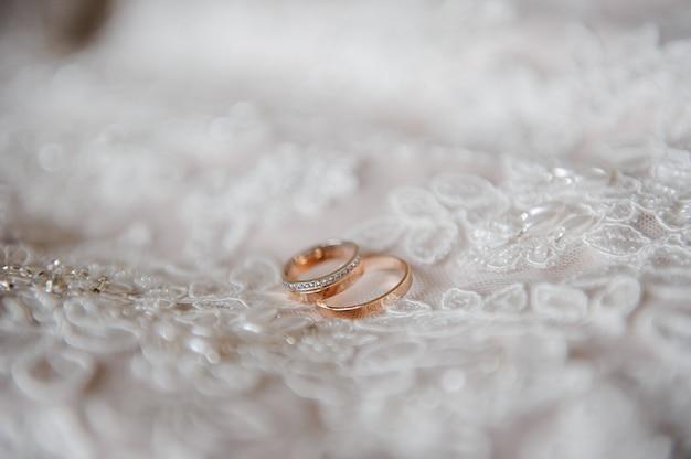Anneaux de mariage sur la robe de mariée.