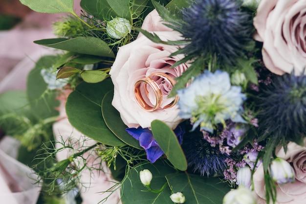 Anneaux de mariage sur une rose dans le bouquet de la mariée