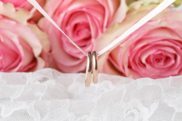 Anneaux de mariage et roses roses