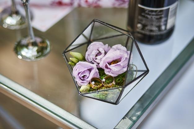 Les anneaux de mariage se trouvent sur une belle boîte avec des fleurs comme accessoires de mariée