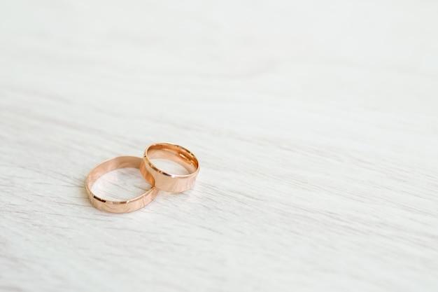 Anneaux de mariage sur une surface en bois blanche