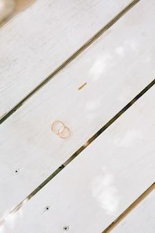 Anneaux de mariage sur une texture en bois blanc