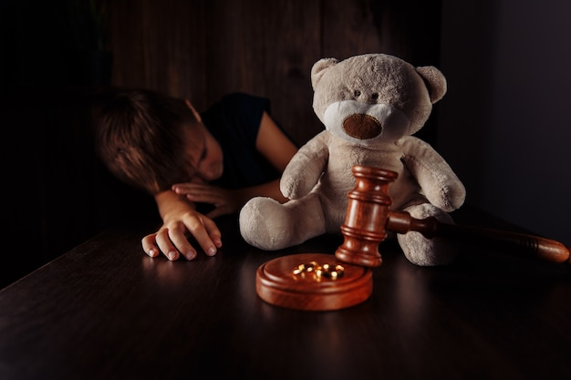 Anneaux de marteau et petit garçon triste avec ours en peluche