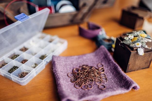 Anneaux métalliques, équipement pour la couture, bracelets sur table en bois, gros plan. bijoux faits à la main. artisanat, fabrication de bijouterie